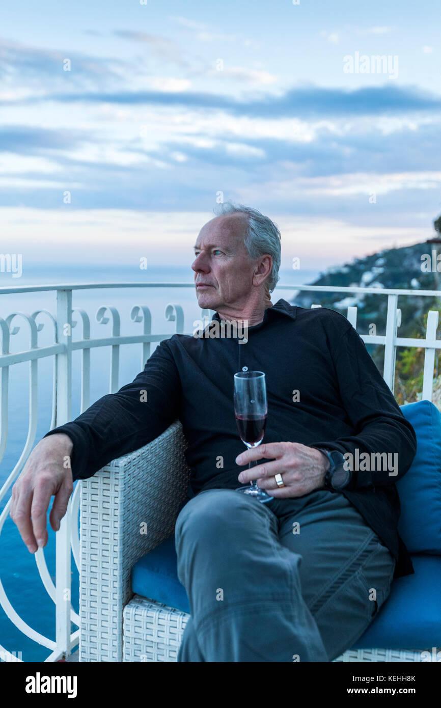 Kaukasische mann Wein trinken und am Wasser Balkon Stockbild