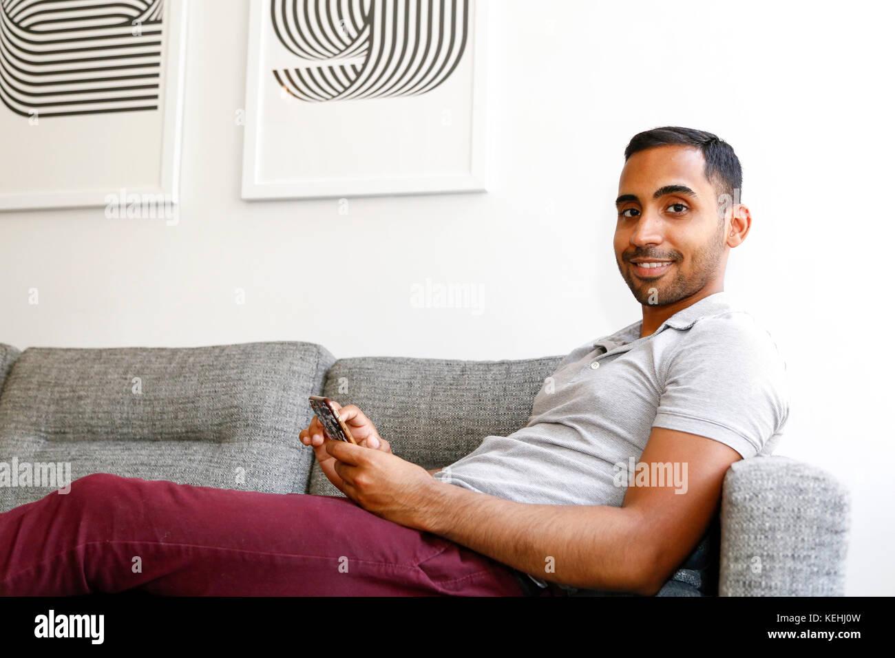 Gemischten rennen Mann auf dem Sofa sitzen auf Handy Simsen Stockbild