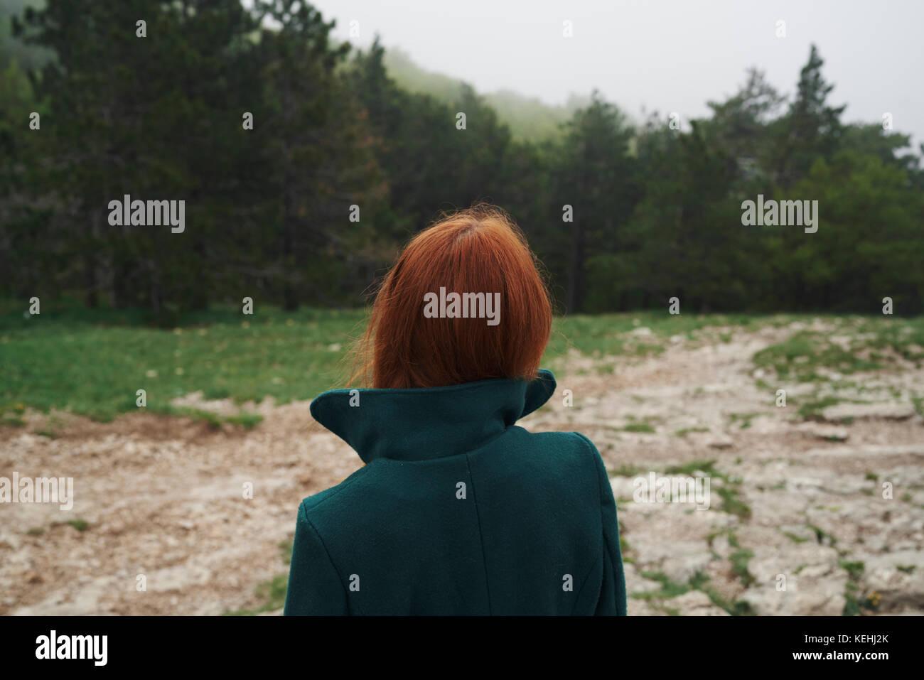 Kaukasische Frau trug einen Mantel mit Kragen im Feld Stockbild