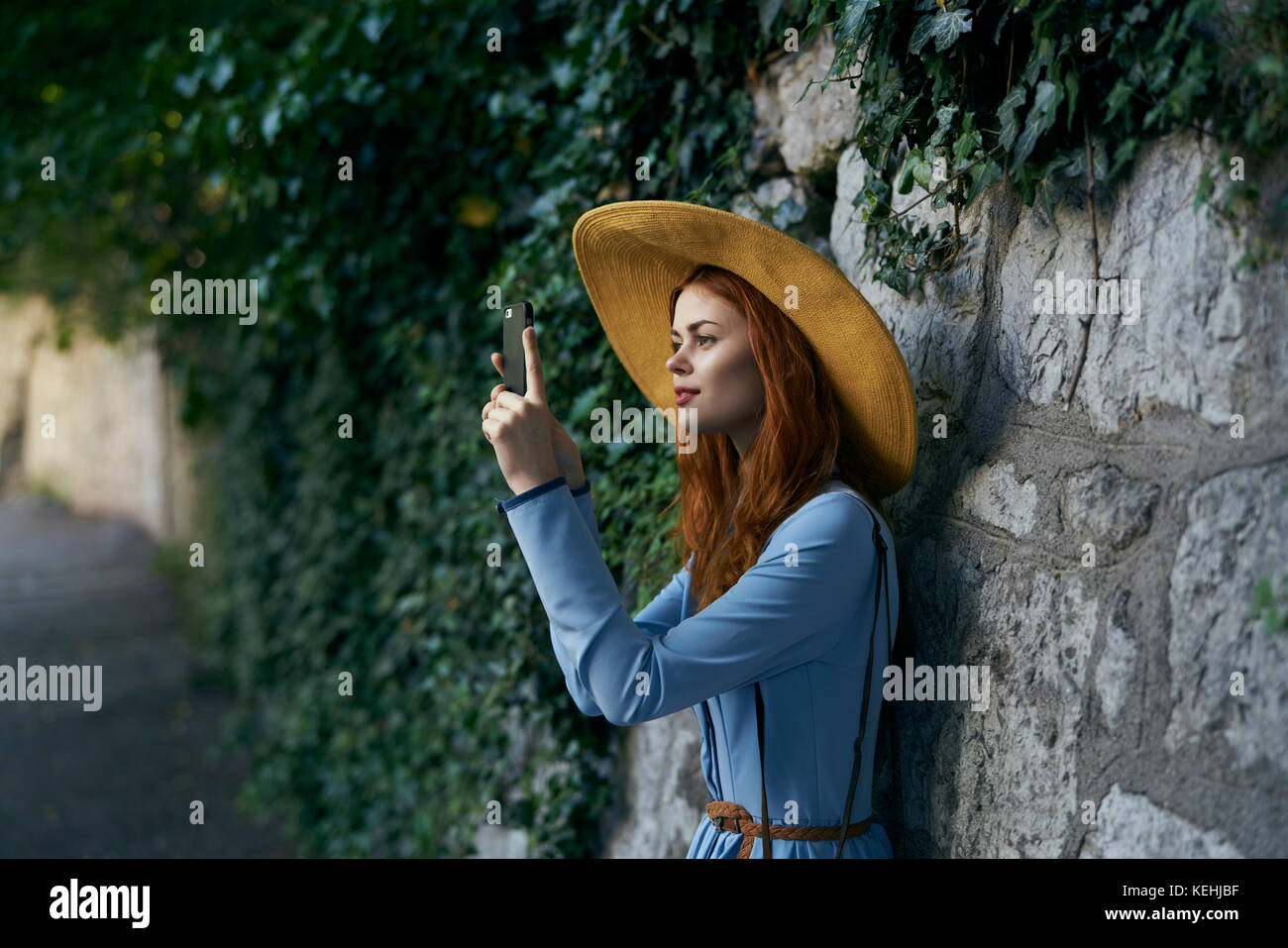 Kaukasische Frau fotografieren mit Handy in der Nähe von Stone Wall Stockbild