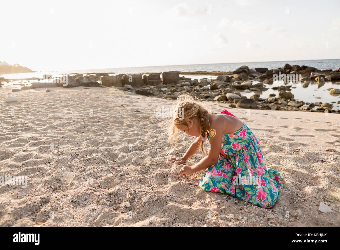 Kaukasische Mädchen spielen im Sand am Strand Stockbild