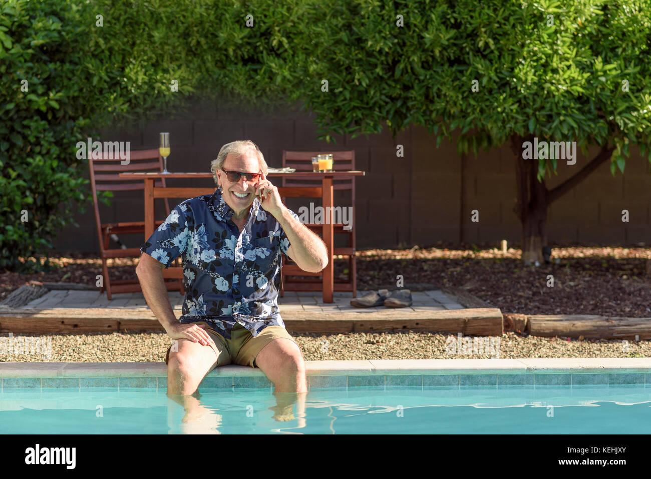 Kaukasische Mann auf Handy mit den Beinen im Pool Stockbild