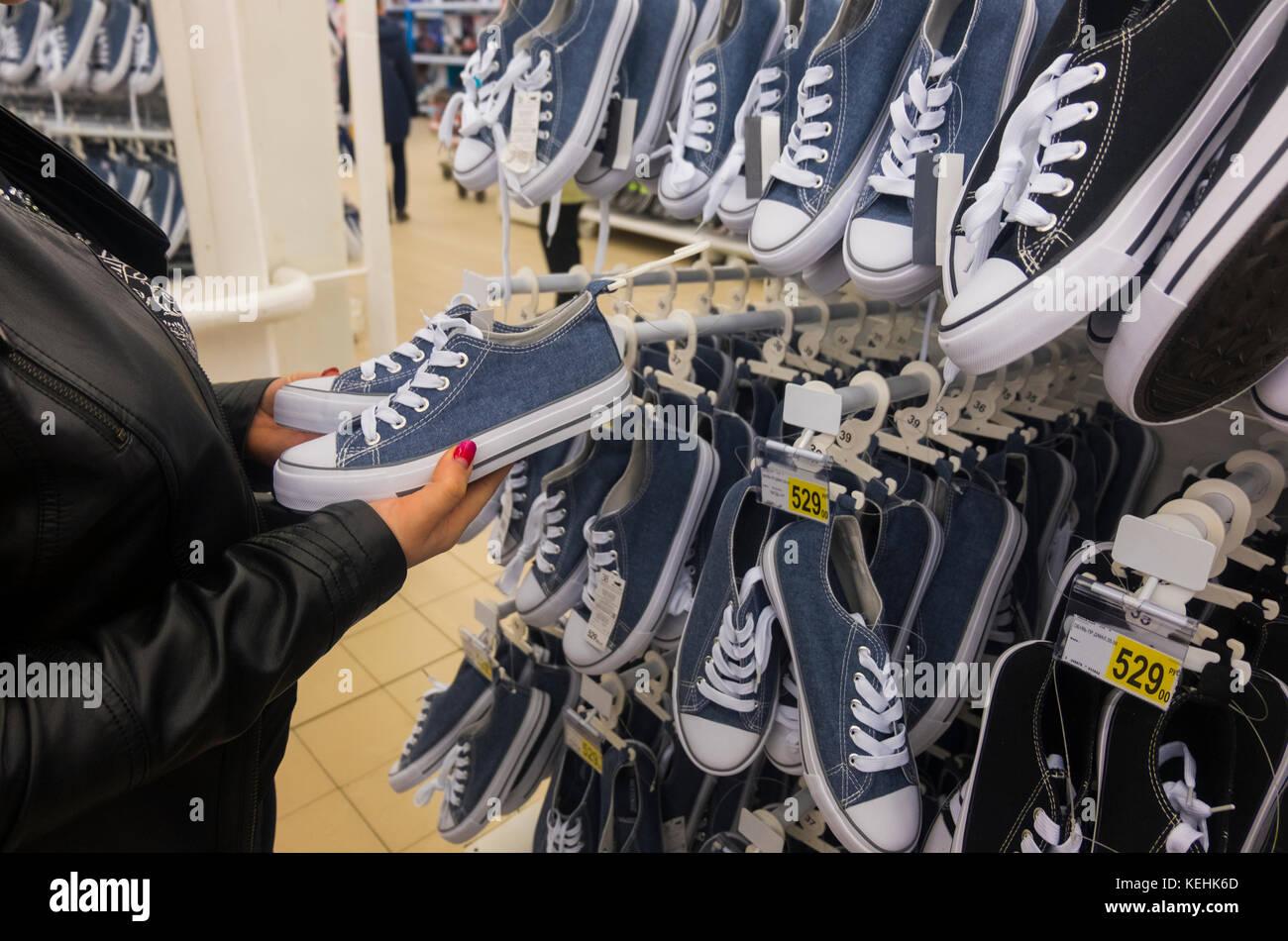 Die Hände der kaukasischen Frau mit Sneakers in Store Stockbild