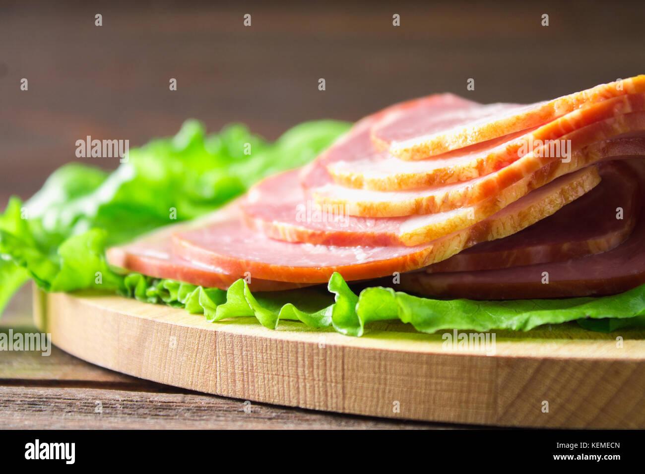 Schinken mit frischen grünen Salatblätter auf einem runden Schneidebrett. Fleischerzeugnisse auf braunem Stockbild