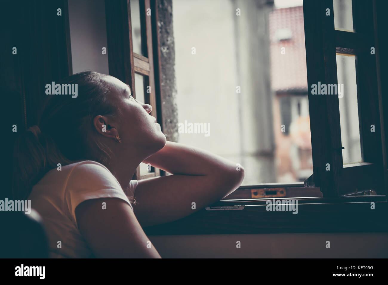 Lonely nachdenkliche Frauen mit nachdenklichen Ausdruck in Gedanken denken und suchen in geöffneten Fenster Stockbild