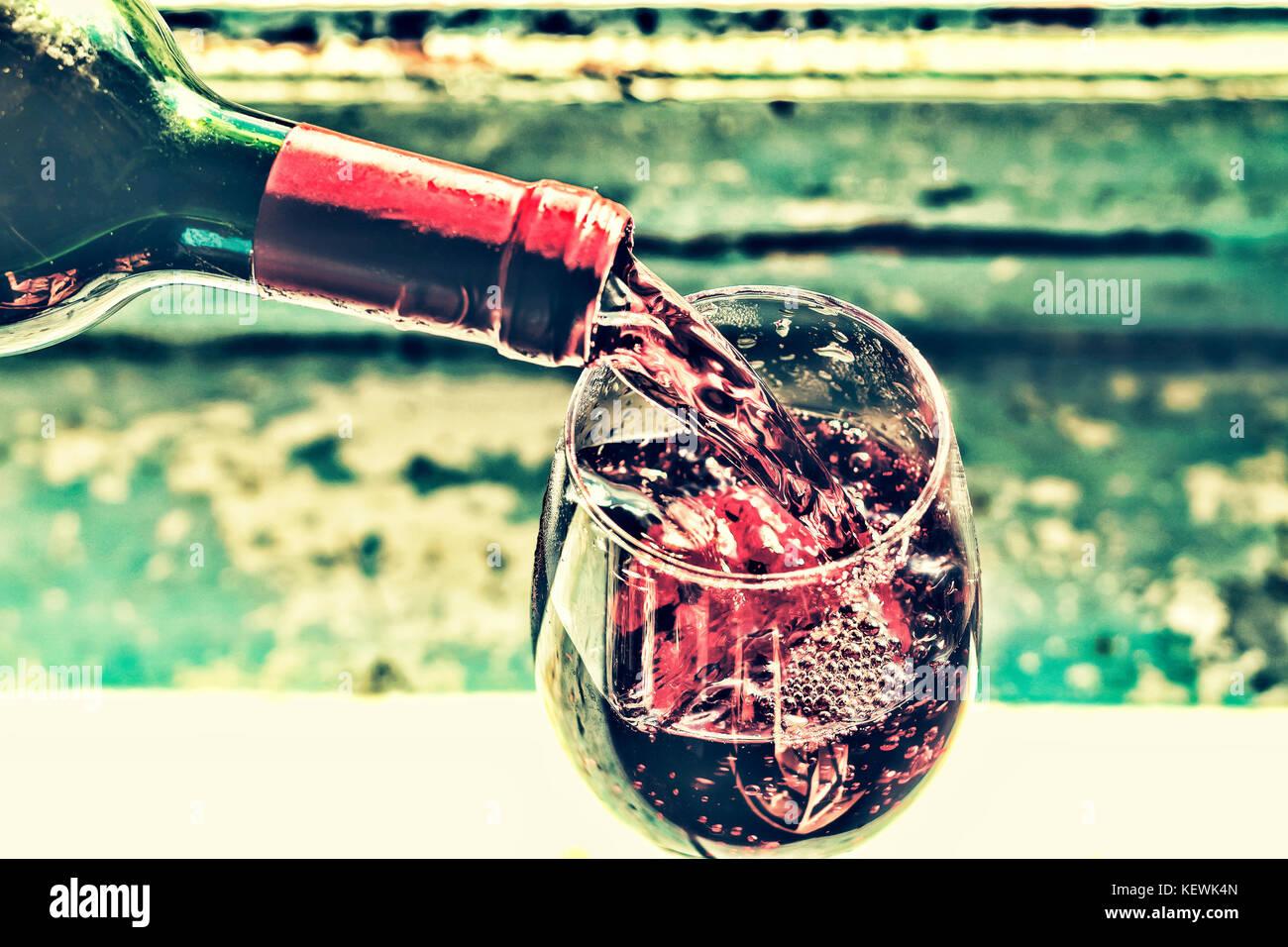 Weihnachten, Neujahr. Gießen rot Wein. Wein in ein Glas. selektive Fokus, Bewegungsunschärfe, Rotwein Stockbild