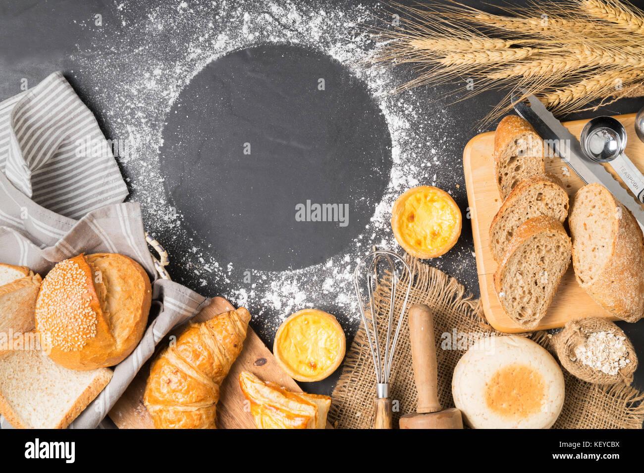 Mix Brot, Croissant, Baguette, Muffin und Ei tart auf schwarzem Stein, Ansicht von oben kopieren und Platz für Stockbild
