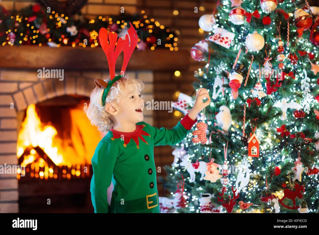 Kind am Weihnachtsbaum und Kamin auf Heiligabend. Familien mit ...