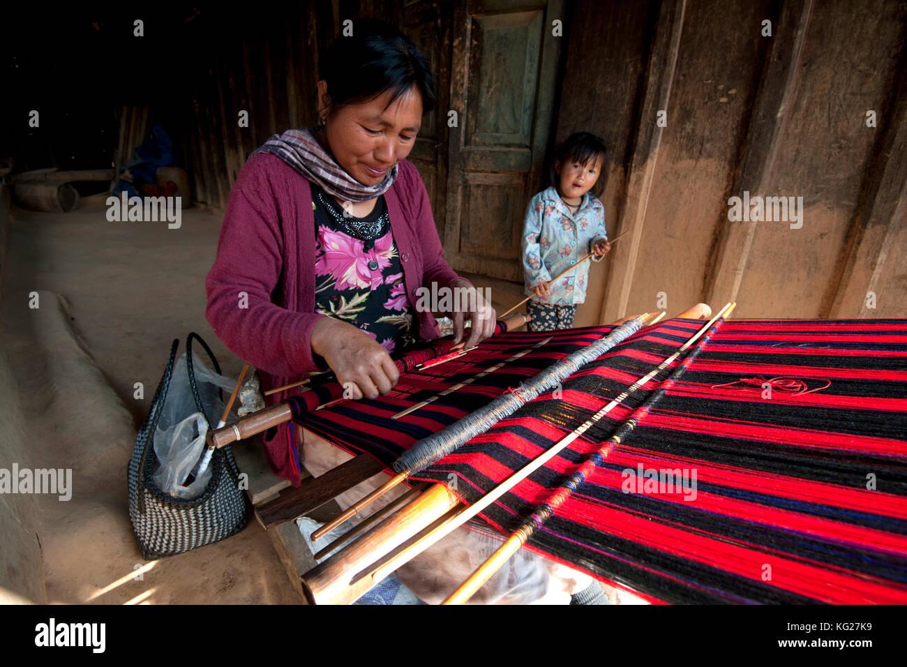 Frau weben traditionelle rote Naga Schal, junge Tochter neben ihr, auf der Veranda der Familie zu Hause, Nagaland, Stockbild