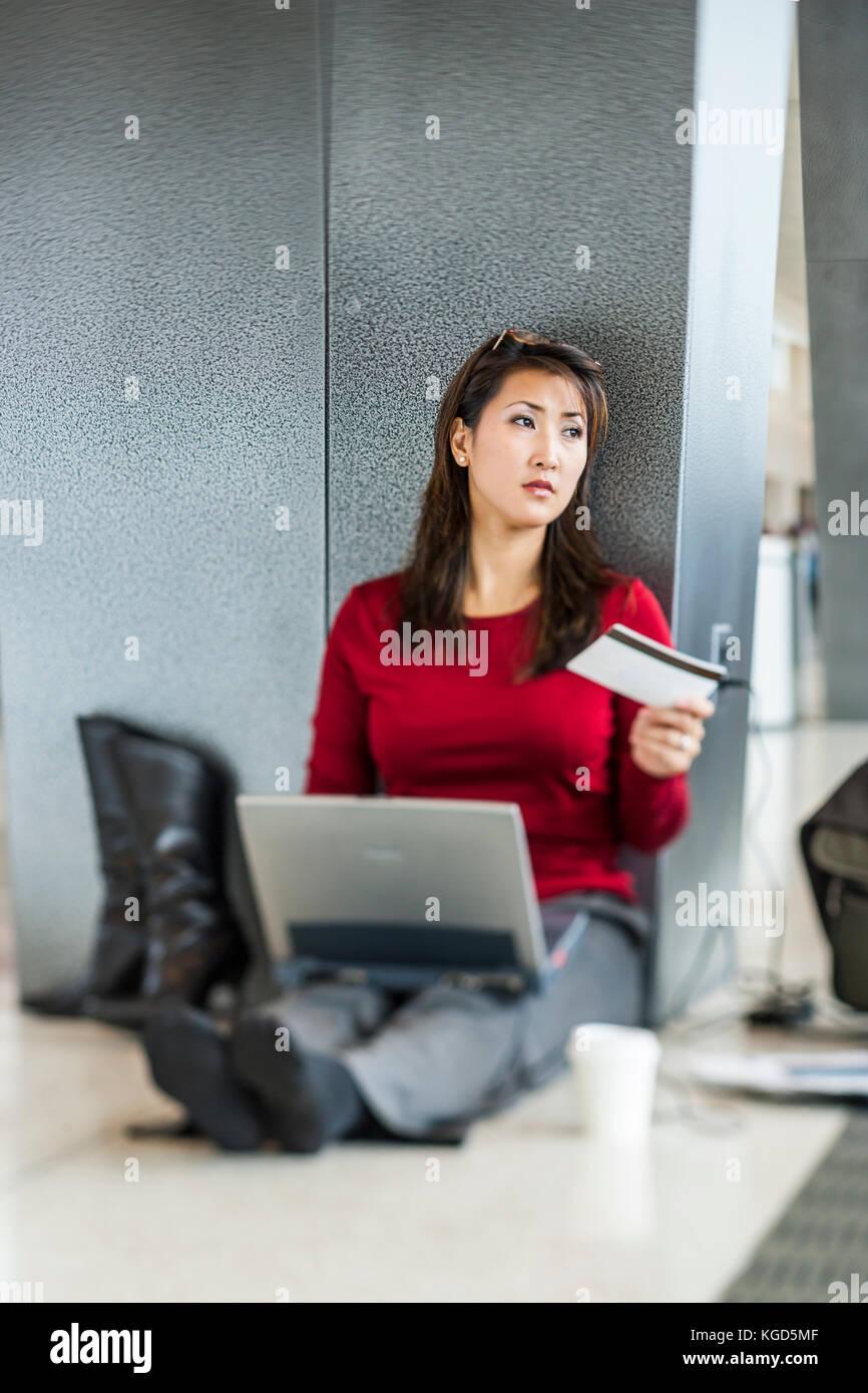 Eine Geschäftsfrau auf dem Fußboden sitzen an Ihrem Abfluggate an einem Flughafen arbeiten an Ihrem Computer. Stockbild