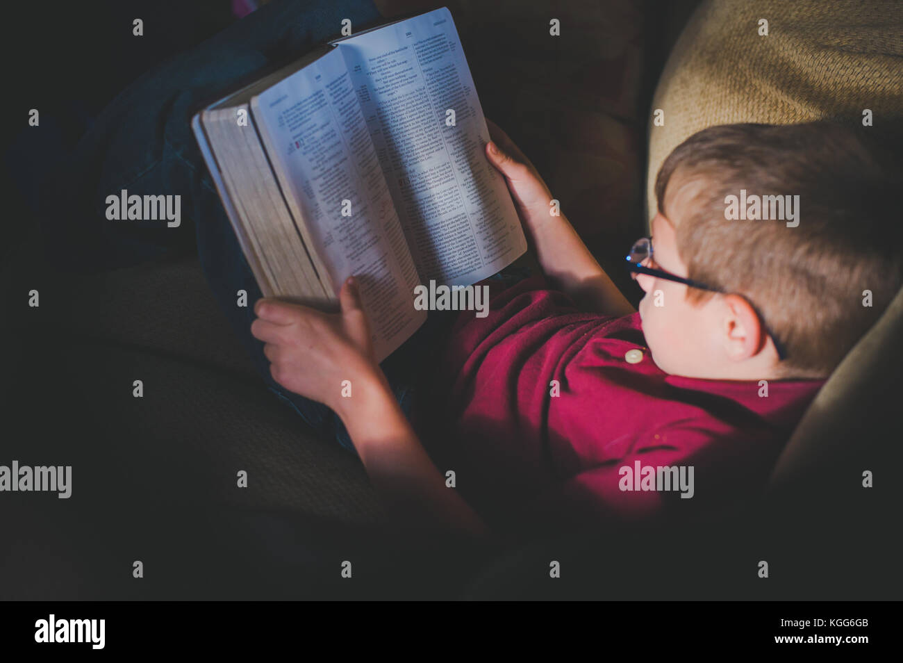 10-11 Jahre alter Junge, ein Buch zu lesen Stockbild