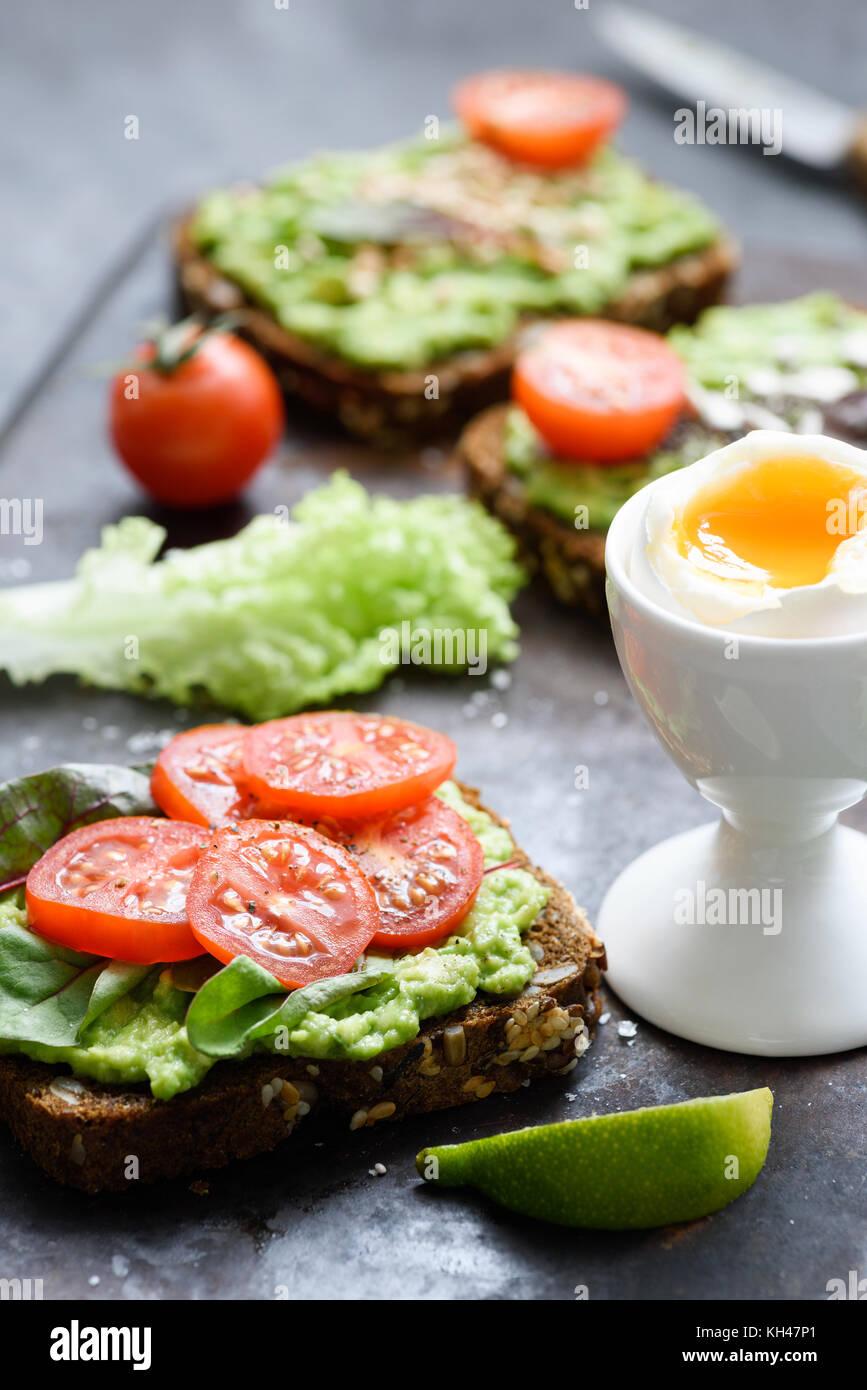 Avocado Toast mit Spinat, Tomaten und gekochtem Ei. Gesunden grünen veggie Sandwich. Selektiver Fokus Stockbild