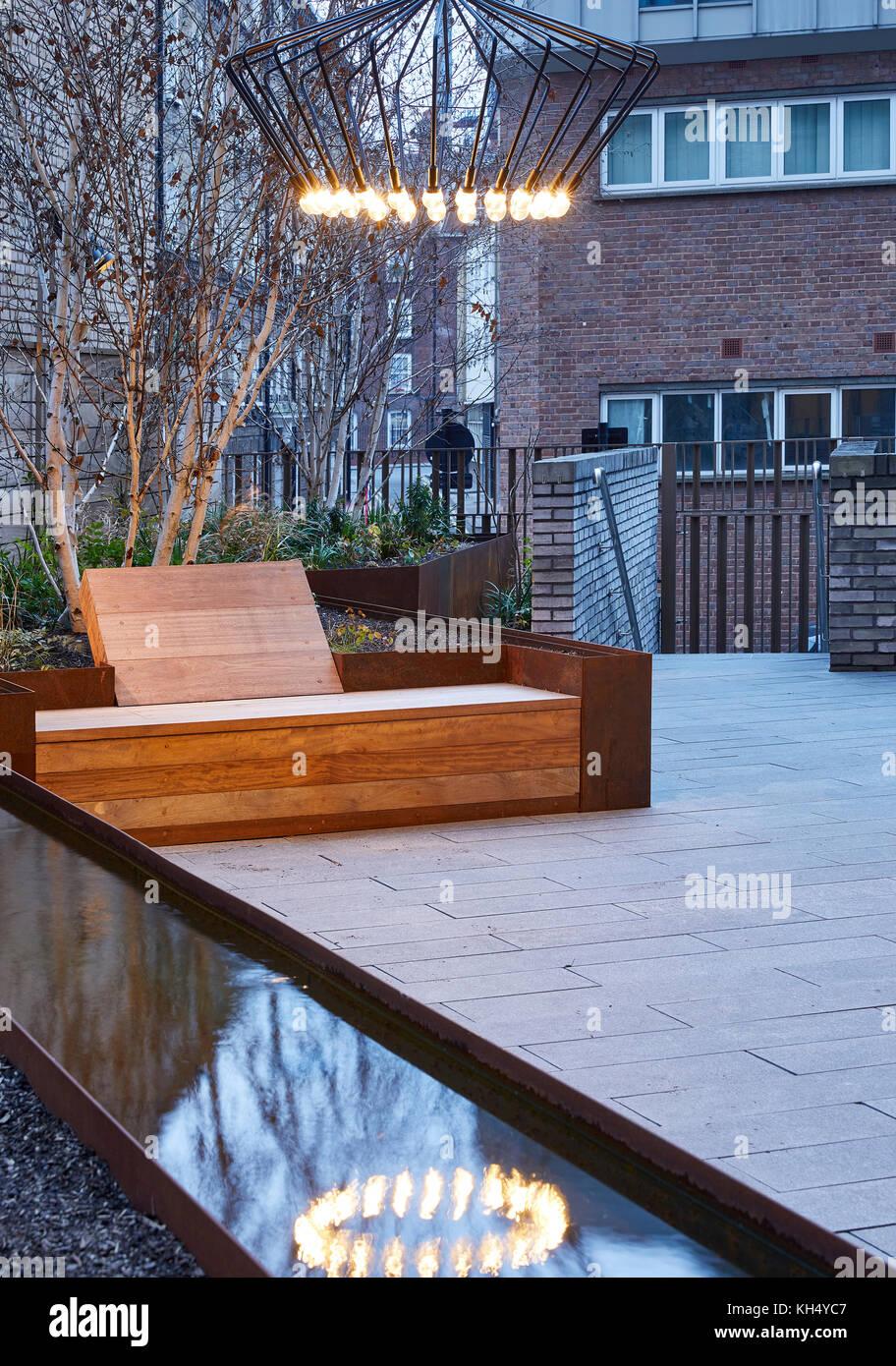 Angelegter Garten mit Beleuchtung und Wasserspiele und hölzernen Sitzgelegenheiten. 55 Victoria Street, London, Stockbild