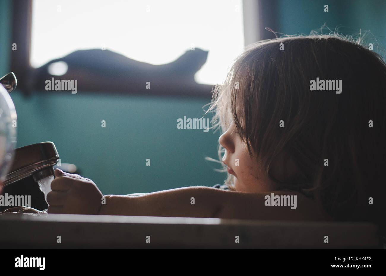 Ein Kleinkind Mädchen waschen Farbe weg die Hände in einem Waschbecken im Bad. Stockbild