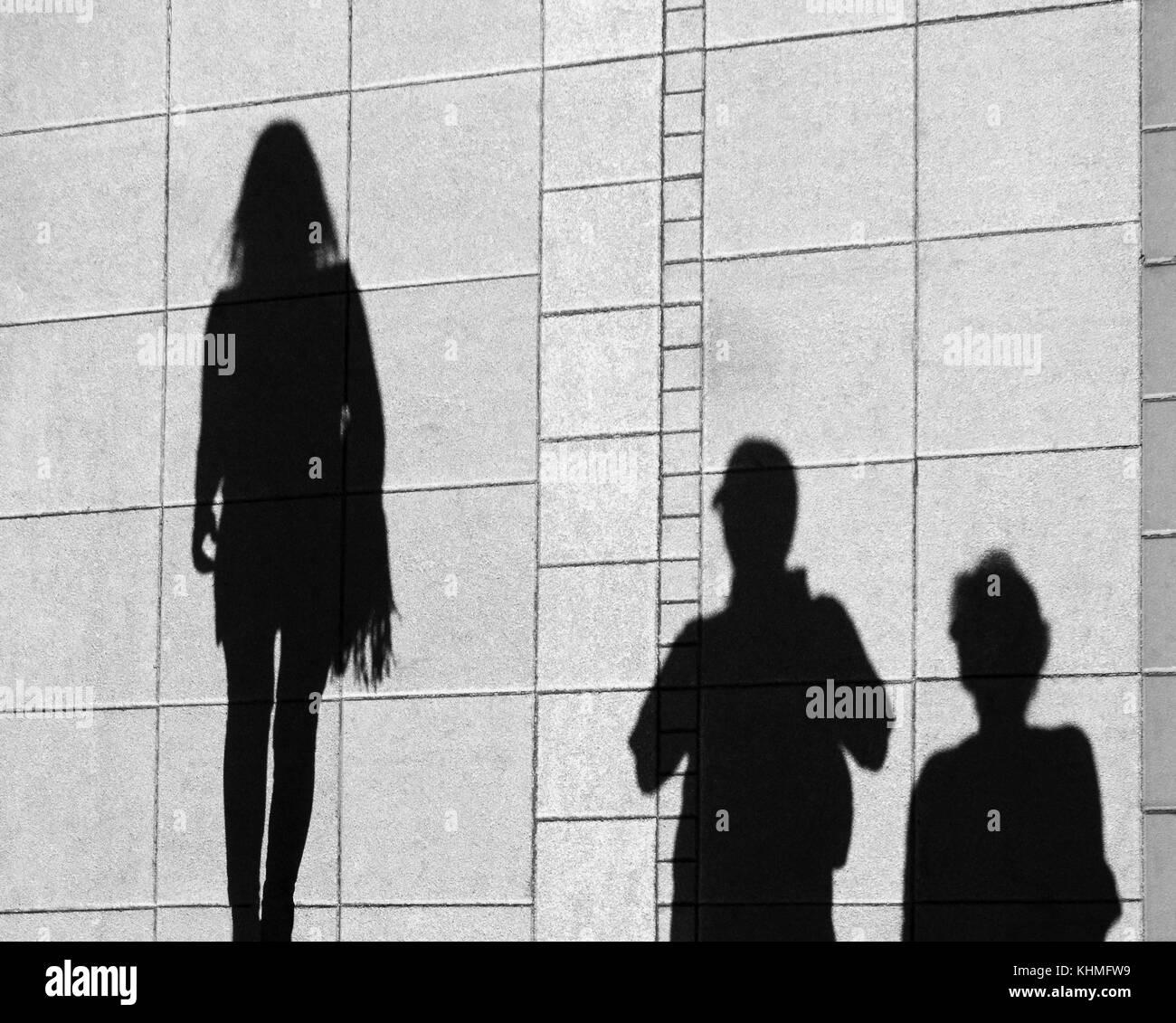 Schatten der Eltern und der Tochter im Teenageralter, die auf Stadt Bürgersteig von oben Stockbild
