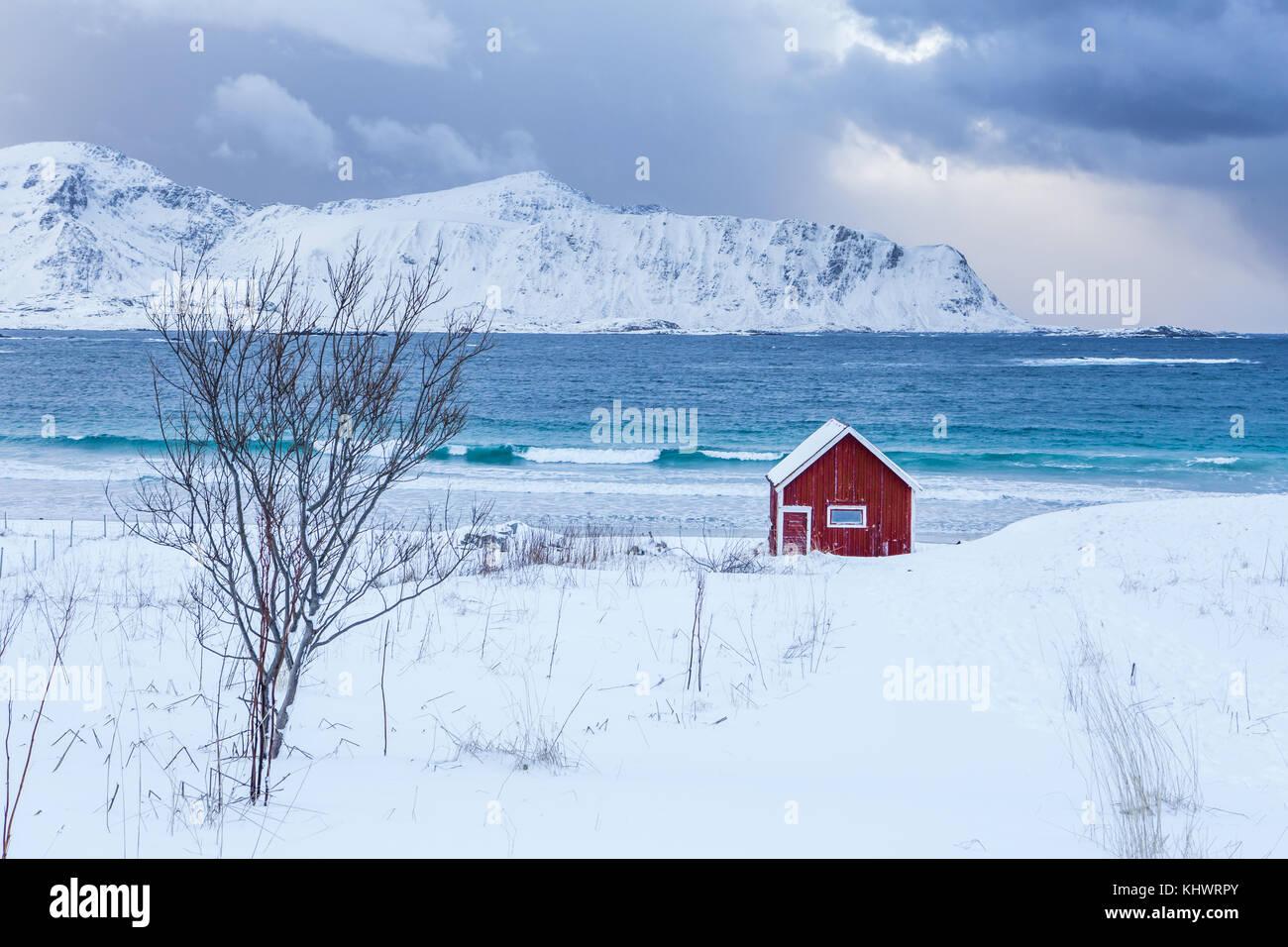 Ein typisches Haus der Fischer namens Rorbu auf den verschneiten Strand Frames der eisigen Meer bei Ramberg Lofoten Stockbild