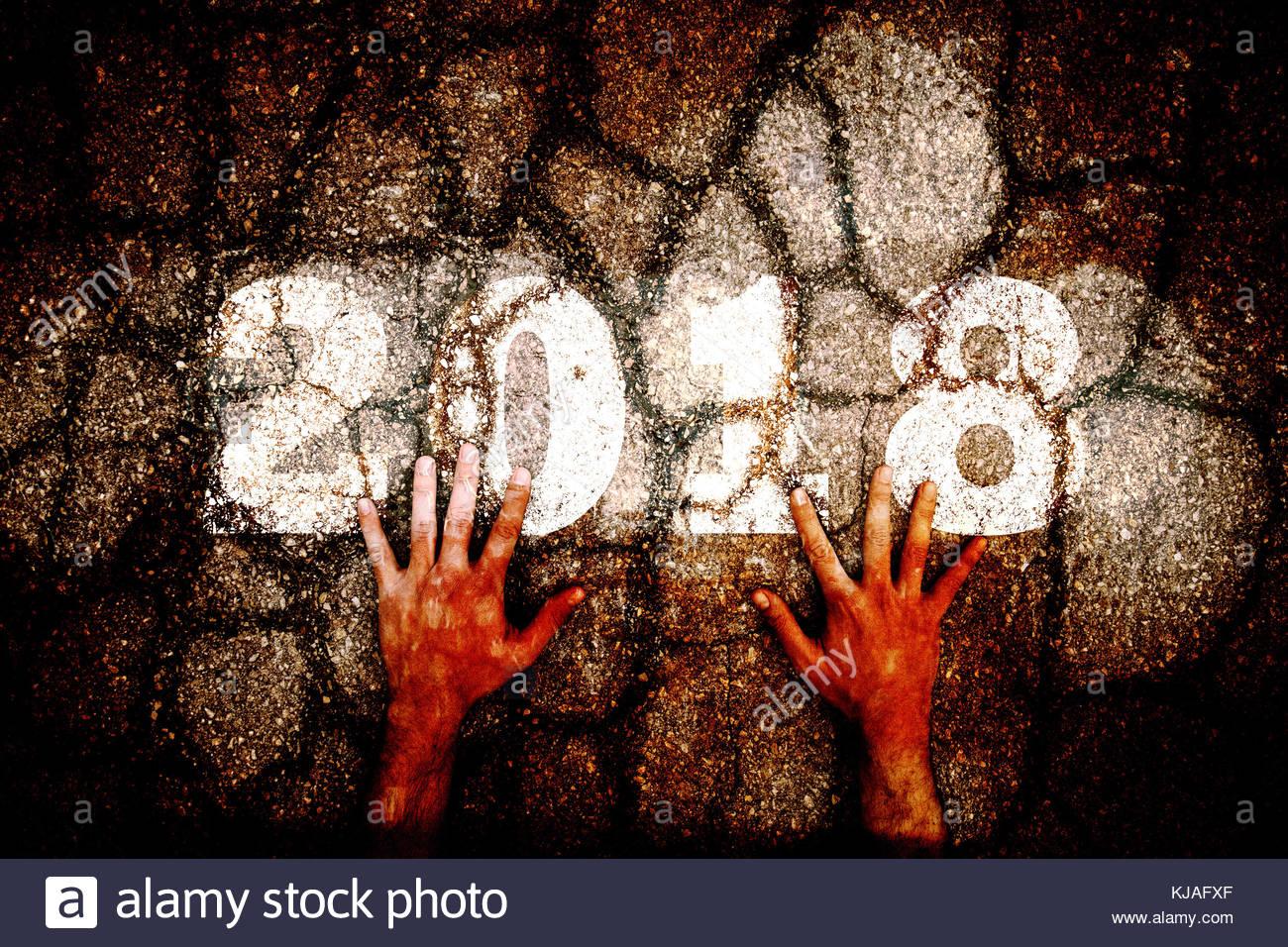 Nahaufnahmen der Hände des Menschen auf Dark grunge Risse im Asphalt Stock mit Jahr 2018 Anzahl gemalt. Stockbild