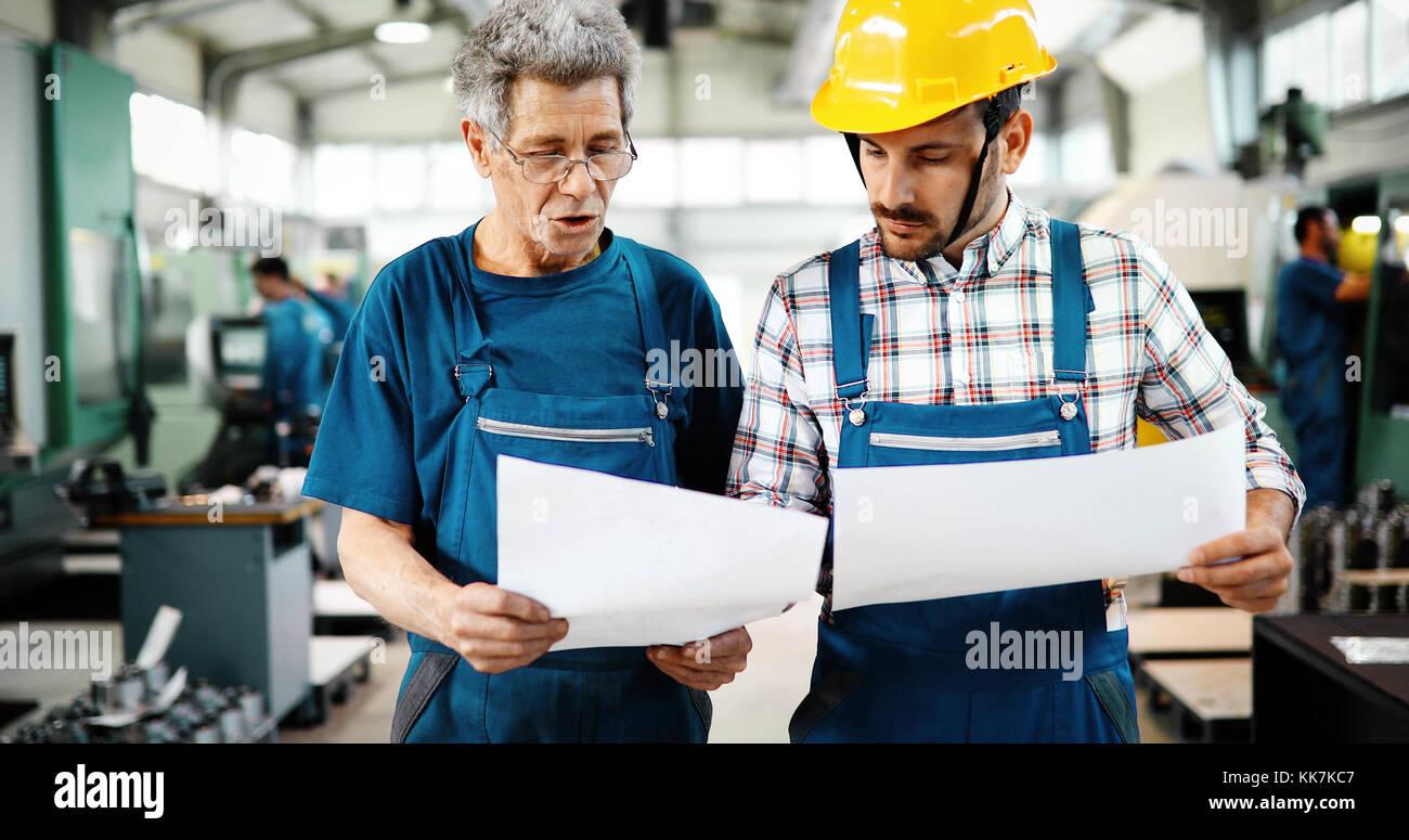 Team von Ingenieuren mit Diskussion In Fabrik Stockbild