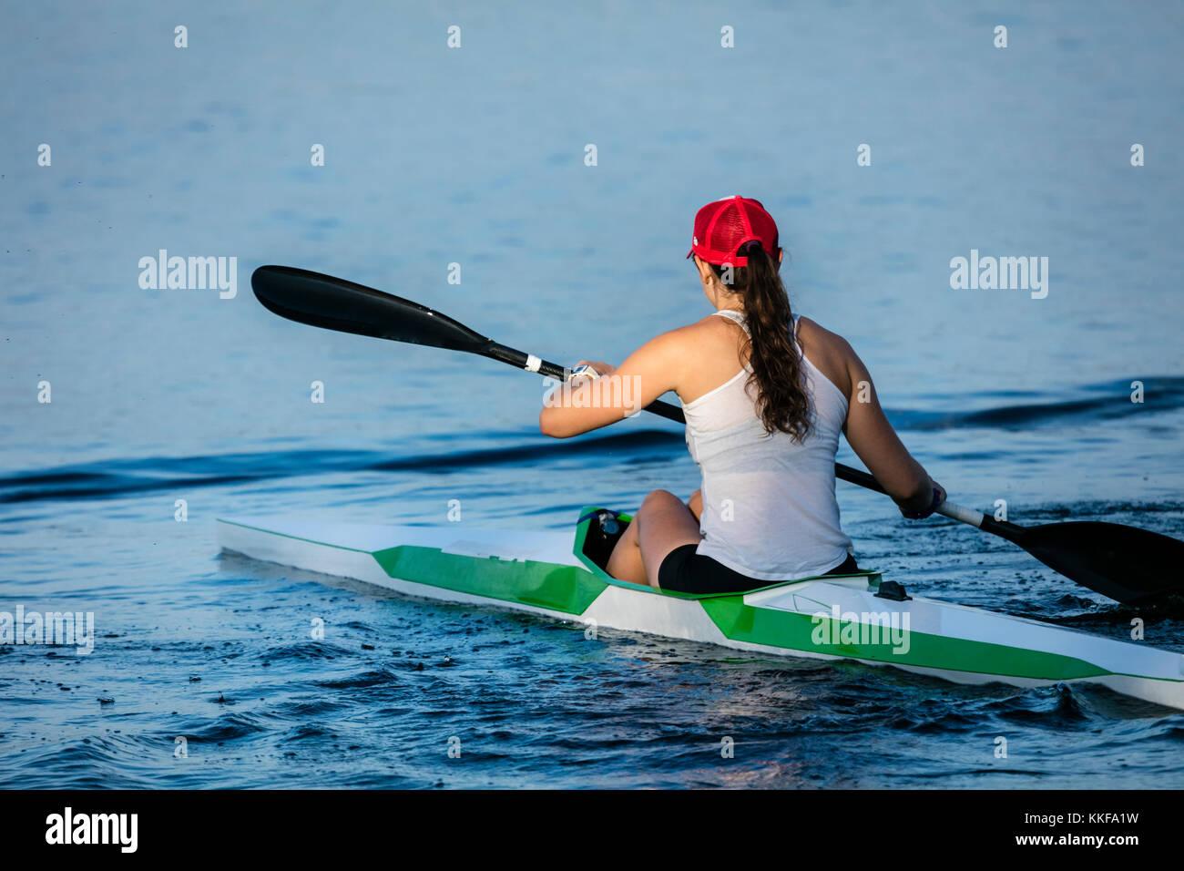 Ein Blick auf eine junge Frau ein Kajak paddeln von hinten. Stockbild