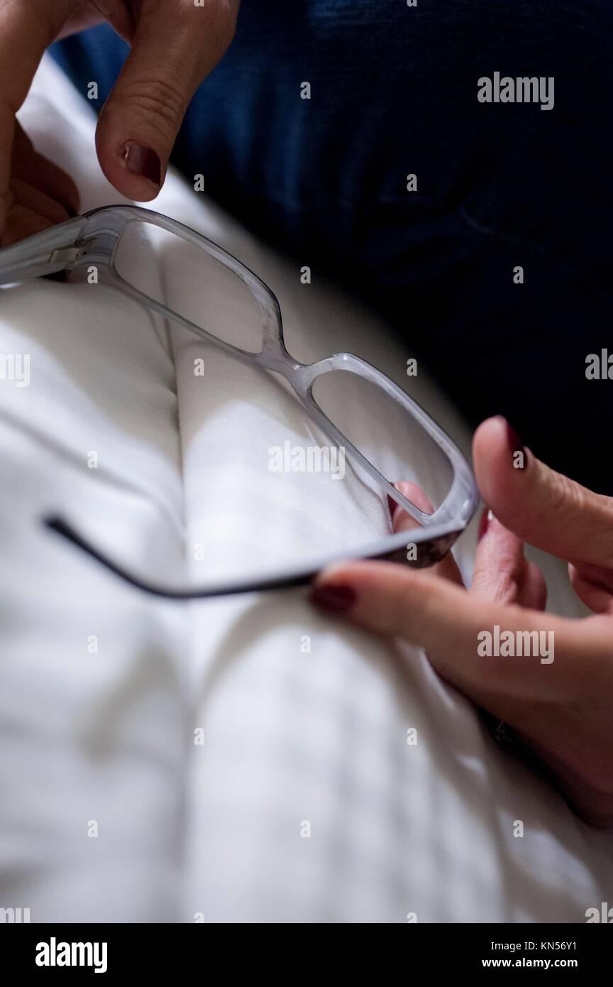 Nahaufnahme von Lesebrille auf Bettwäsche in der Frau Finger statt. Stockbild