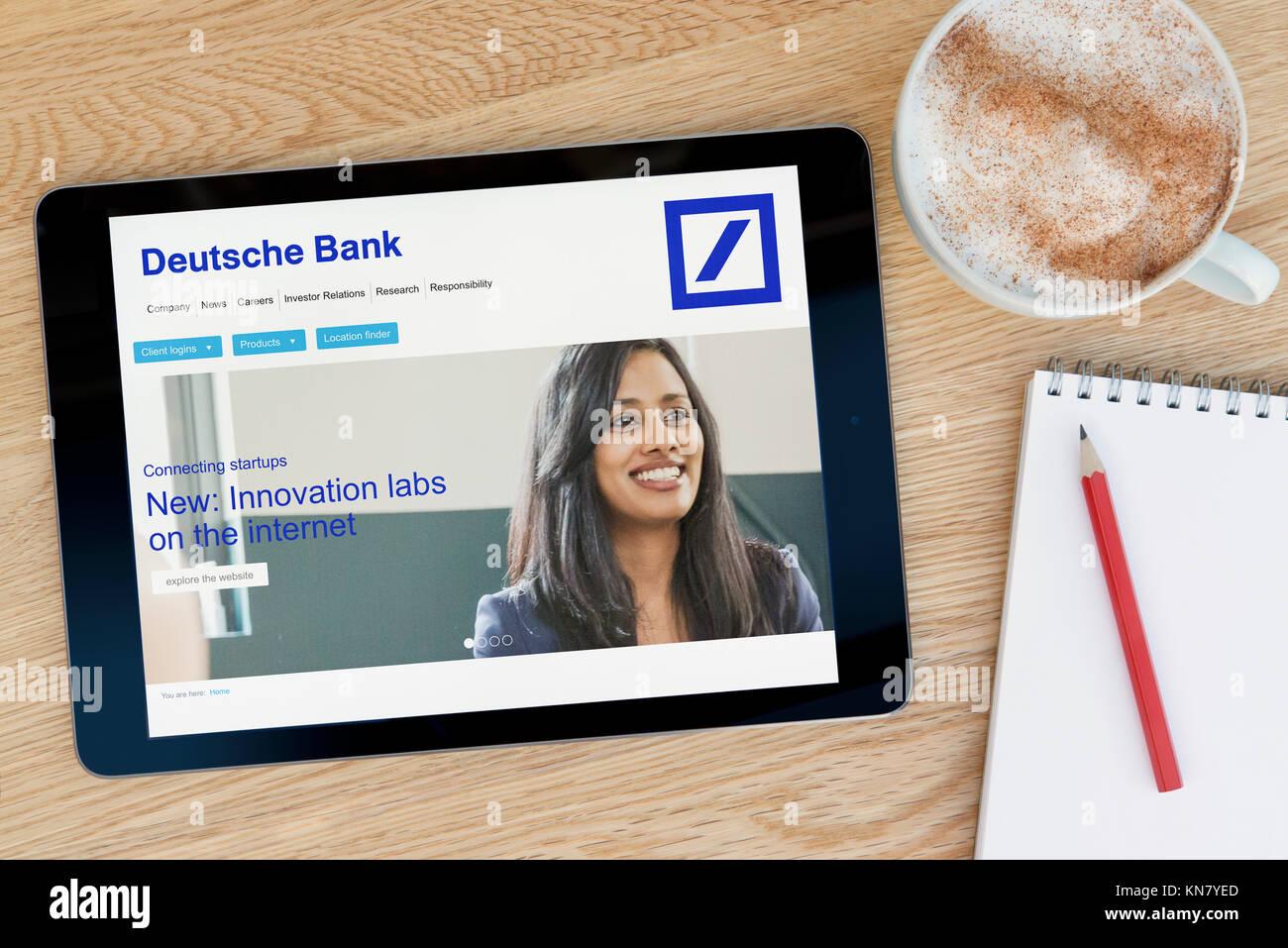 Die Deutsche Bank Website auf einem iPad Tablet Gerät, das auf einem Tisch liegt neben einem Notizblock und Stockbild