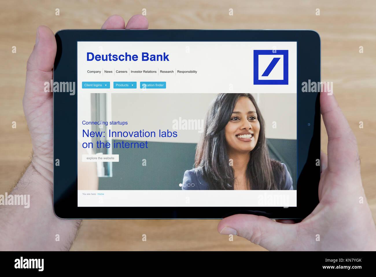 Ein Mann sieht die Deutsche Bank Website auf seinem iPad tablet device, Schuß gegen einen hölzernen Tisch Stockbild