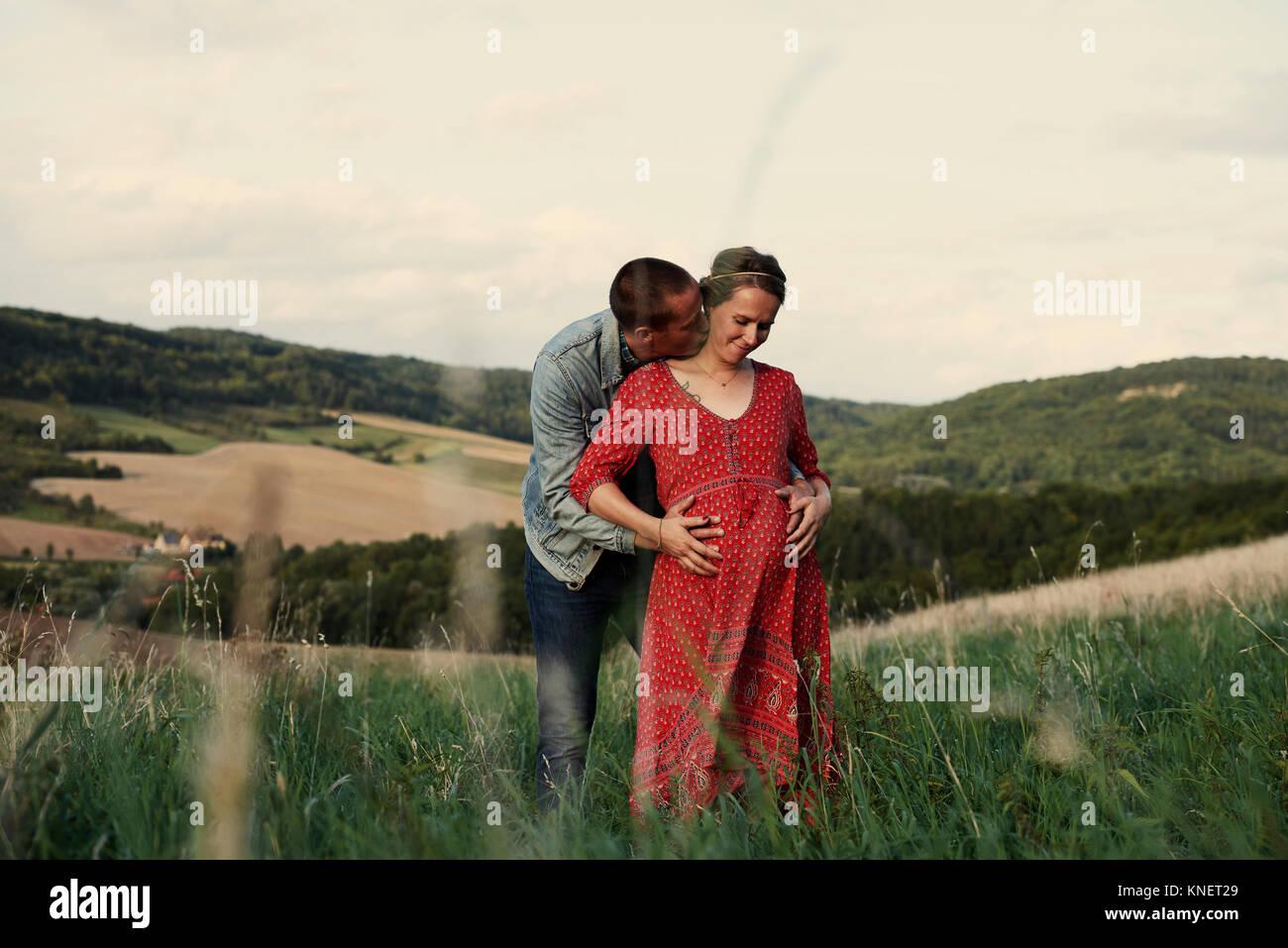 Romantischer Mann mit Hände auf die schwangere Frau Magen im Querformat Stockbild