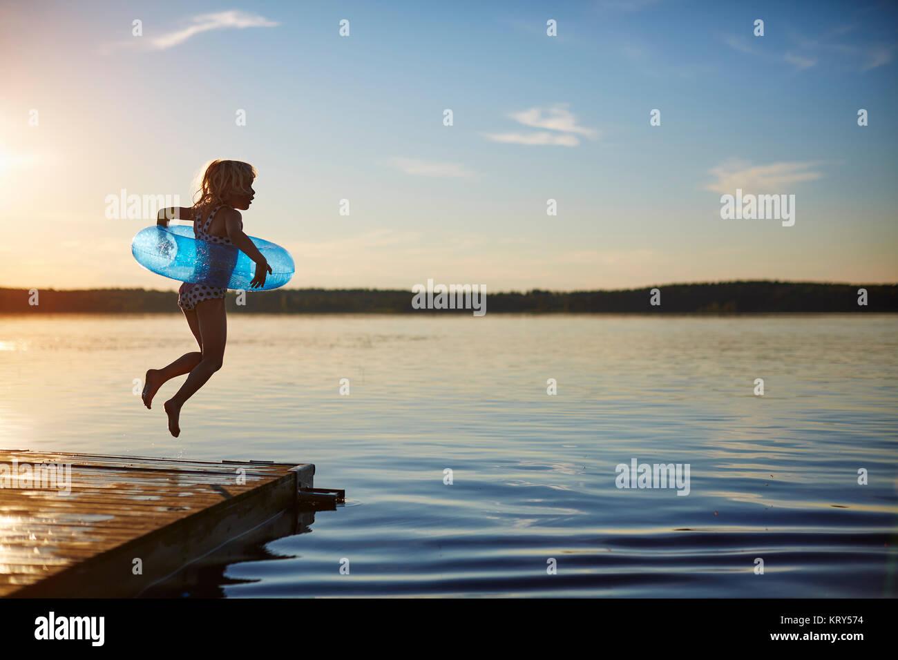 Mädchen springen einem Pier Stockbild