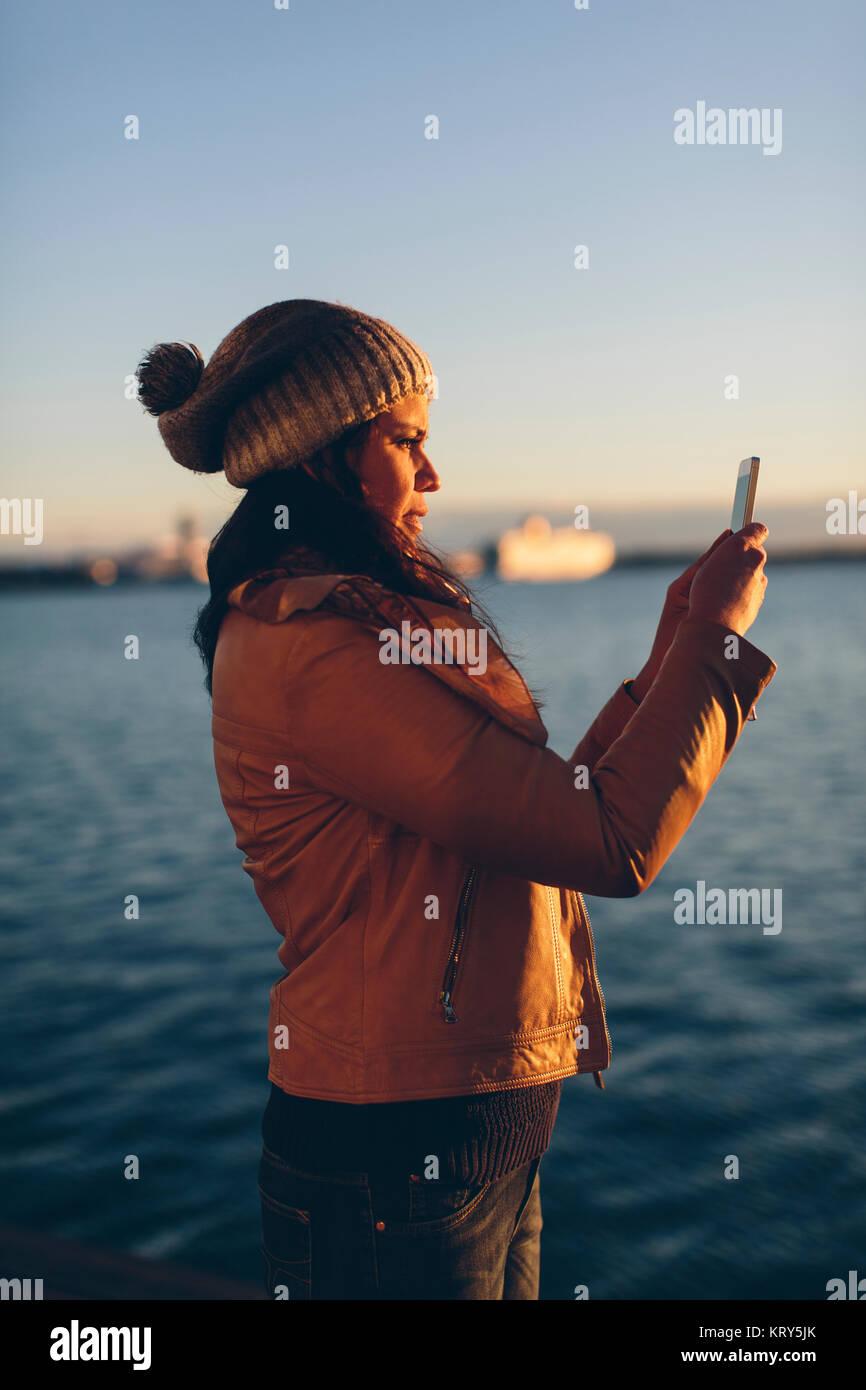 Frau mit einem Smart Phone am Meer Stockbild