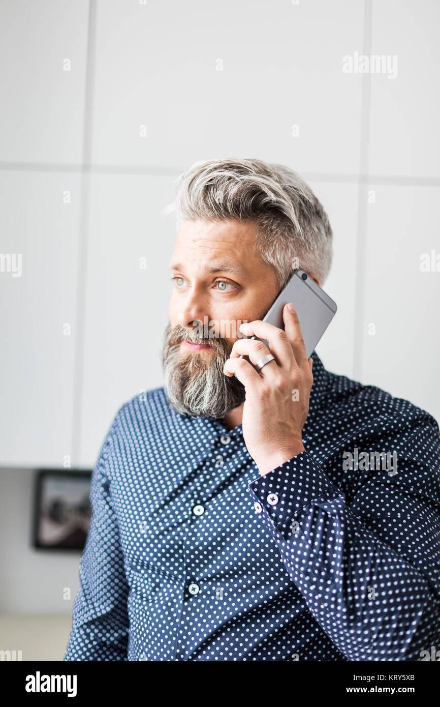 Ein Mann in einem beschmutztes Shirt mit einem Mobiltelefon Stockbild