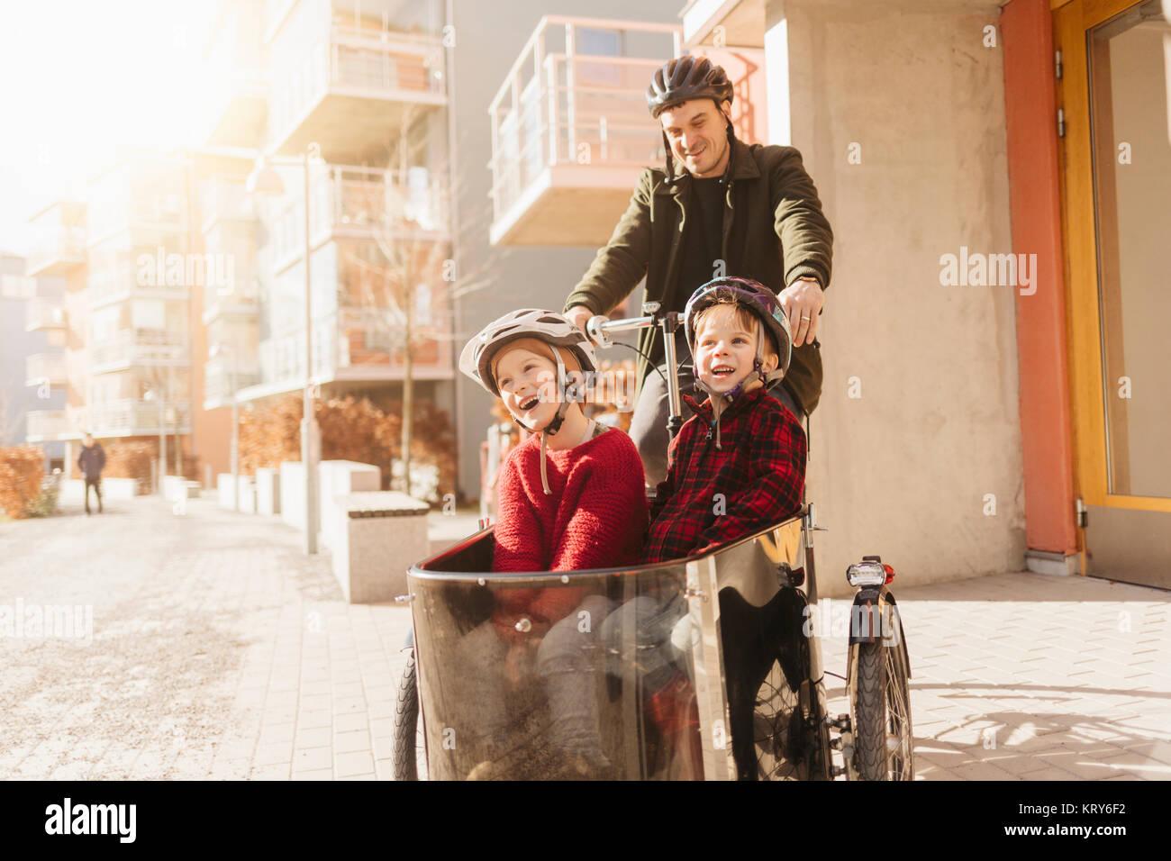 Man Radfahren mit seinen Söhnen in Stockholm Stockbild