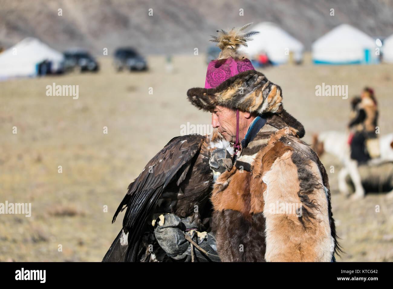 Kasachischen Eagle Hunter verbringt sie Ausfallzeiten mit seinem Adler während Golden Eagle Festival in der Stockbild