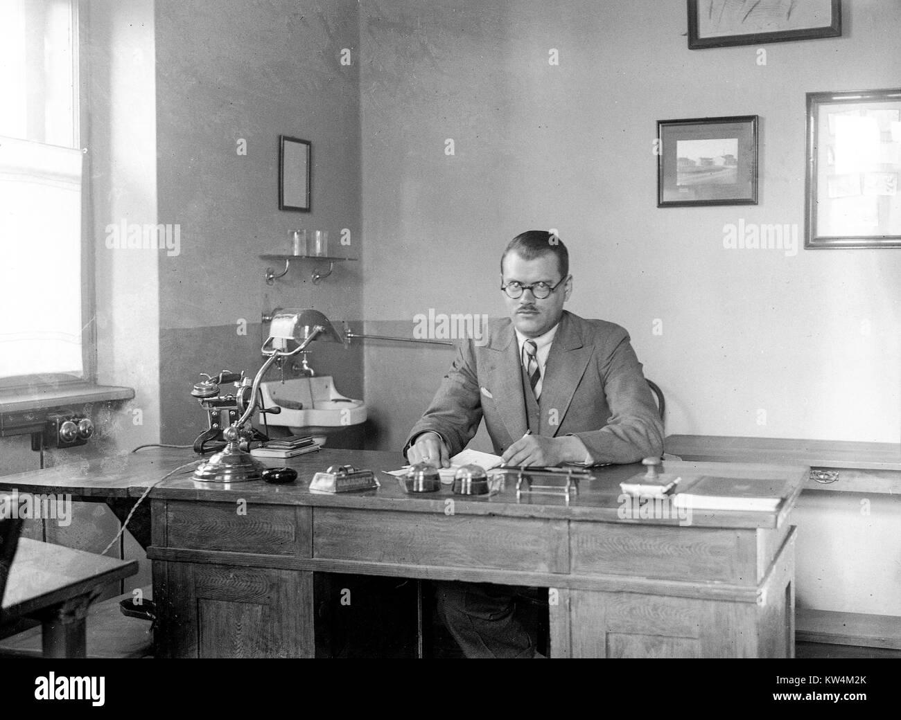 Ein Mann mit kurzen Haaren, runde Brille, eine konservative Anzug ...