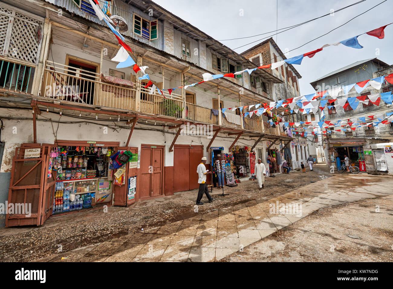 Bunte Fahnen für die Wahlen im Straßenbild mit typischen Gebäude in Stone Town, UNESCO-Weltkulturerbe, Stockbild