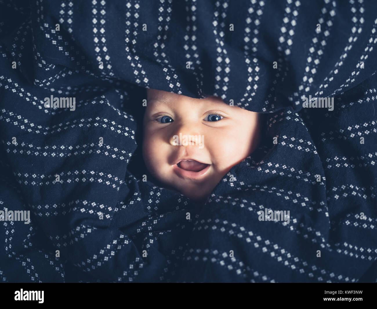 Eine Glücklich lächelnde Baby wird durch Bettzeug bedeckt und nur sein Gesicht sichtbar ist. Stockbild