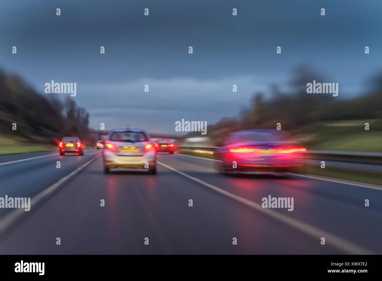 Schnell fahrenden Autos auf einem nassen Britische Autobahn in der Abenddämmerung. Stockbild