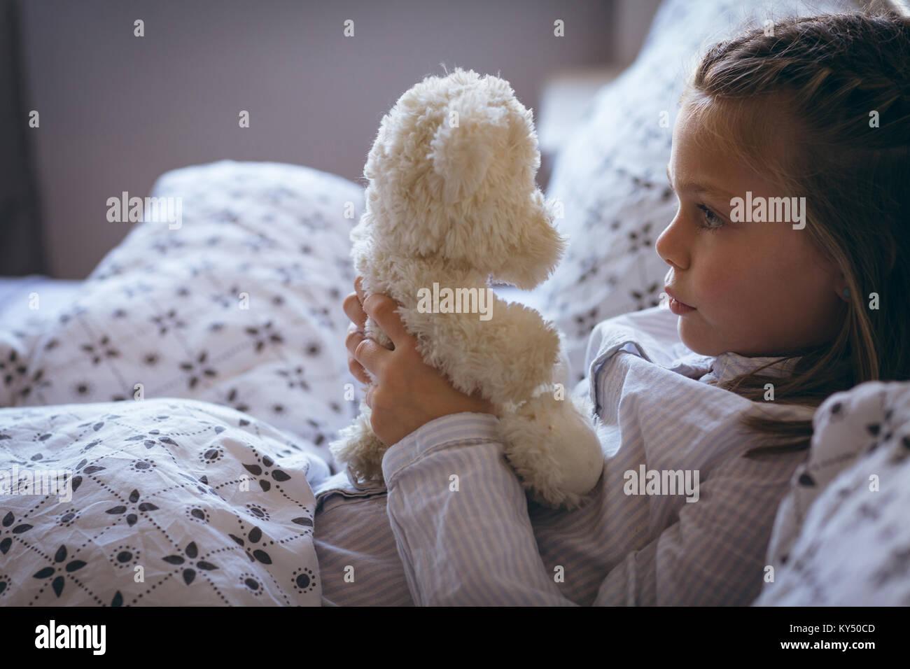 Mädchen mit Teddybär auf Bett Stockbild