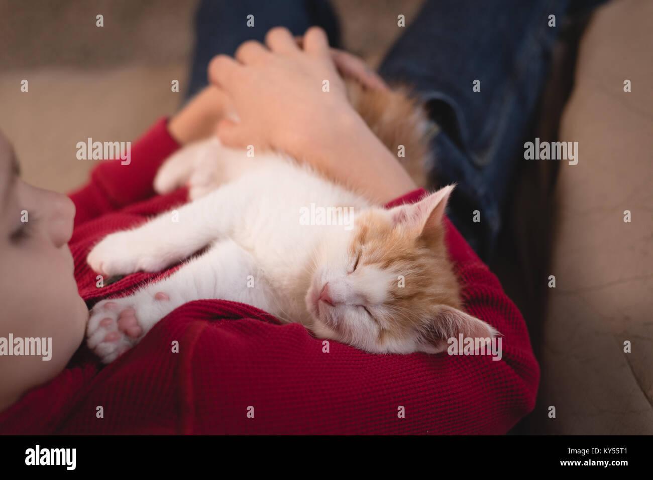 Junge hält Ihre Katze im Wohnzimmer Stockbild