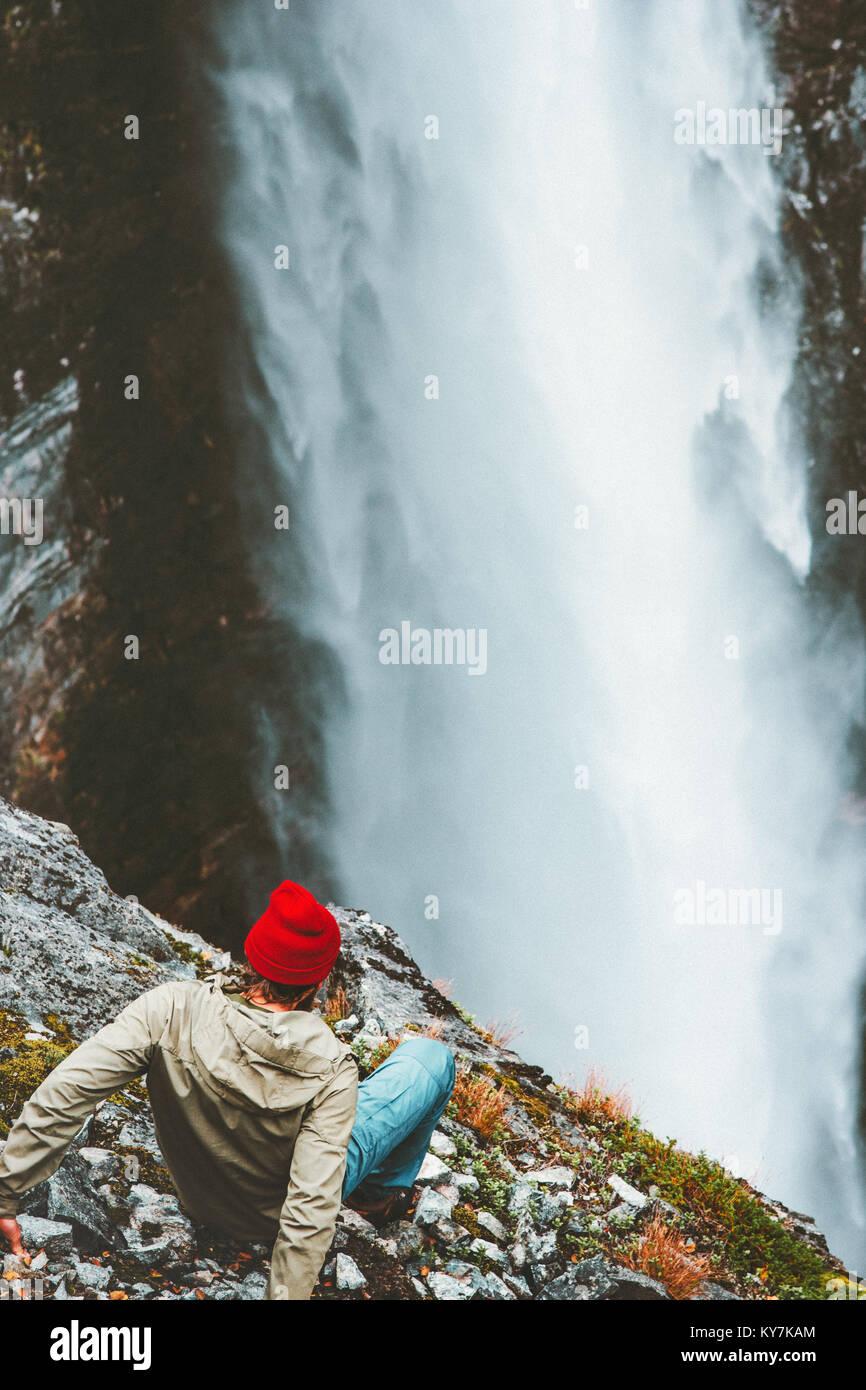 Man Touristen auf Felsen am Wasserfall outdoor Reisen Lifestyle erfolg konzept Abenteuer Ferien in den Bergen Stockbild