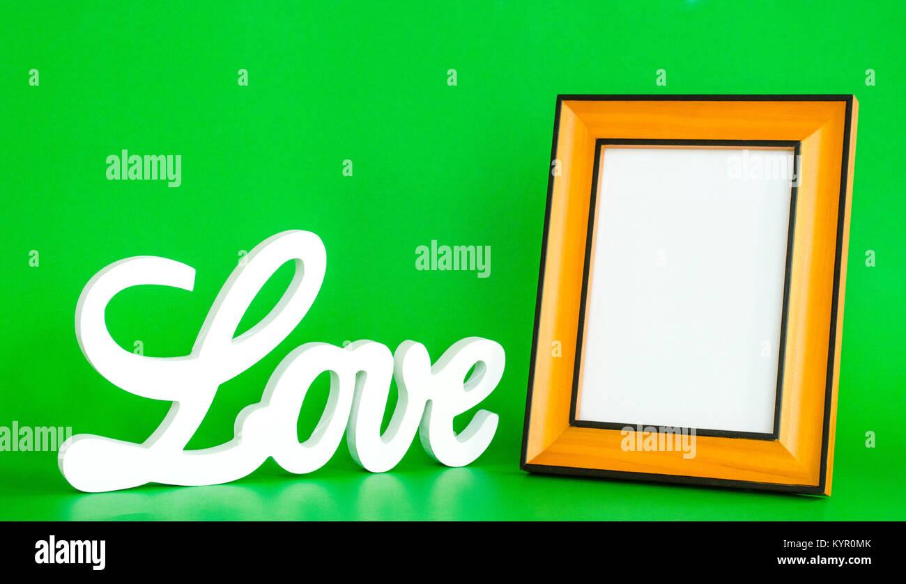Weiß Liebe zeichen Kursiv mit einem leeren Bilderrahmen auf grünem ...