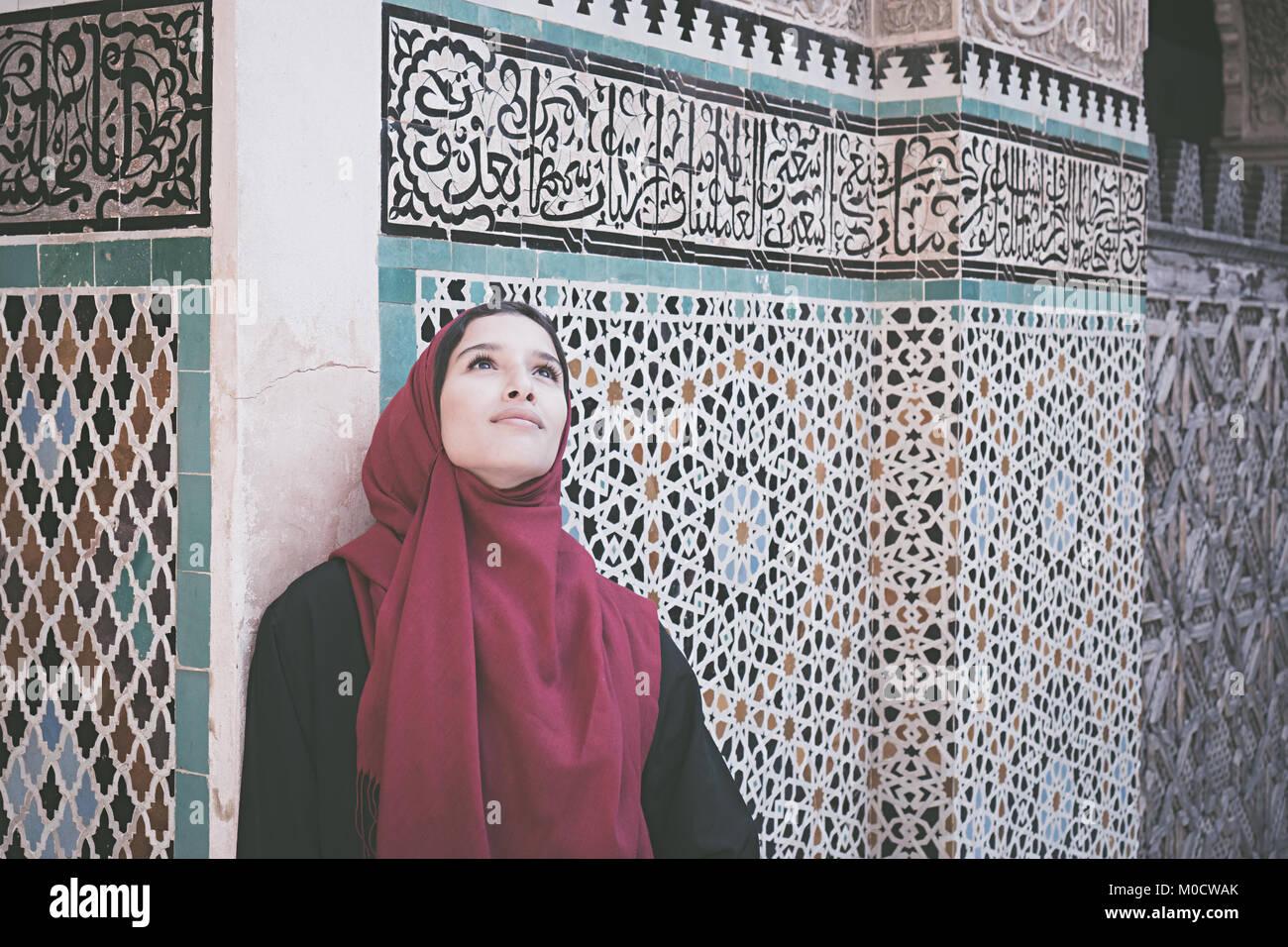 Arabische Frau in traditioneller Kleidung mit roten Kopftuch vor der Wand mit Text aus dem Koran Stockbild