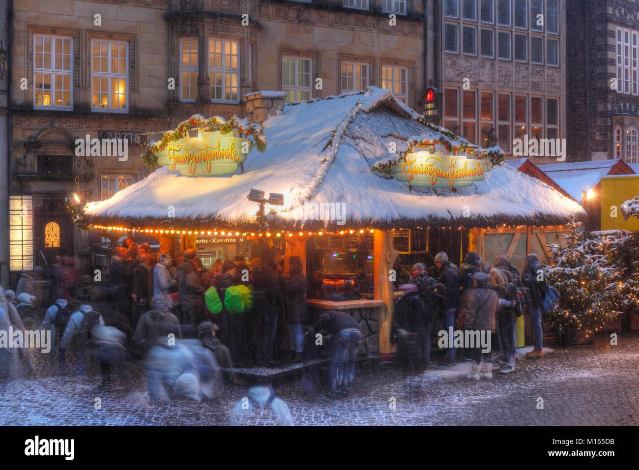 Verschneiter Glühweinstand auf dem Weihnachtsmarkt am Marktplatz bei Abenddämmerung, Bremen, Deutschland Stockbild