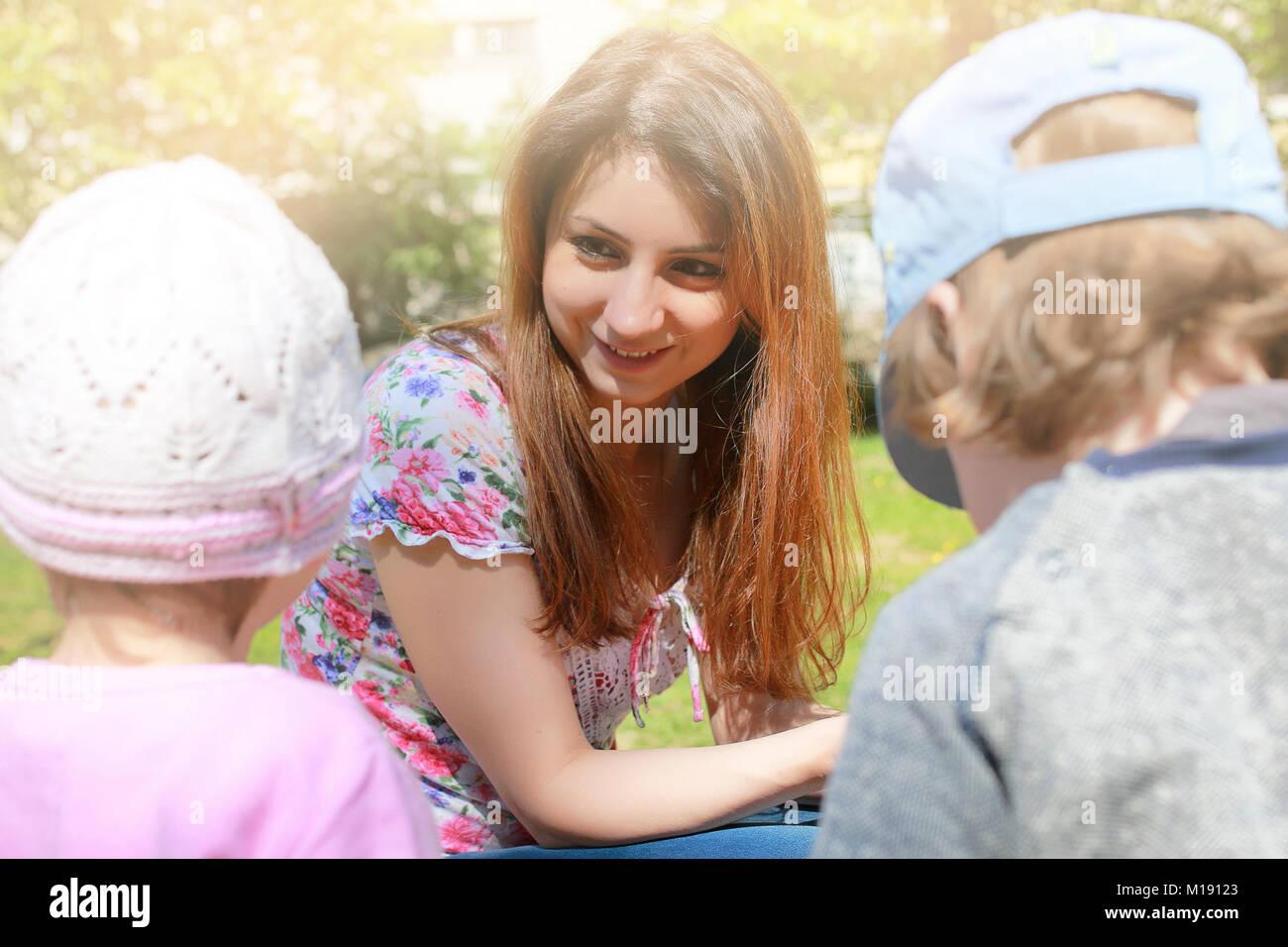 Mama spricht mit Kindern Zwillinge und zu lehren, wie sie zu handeln Stockbild