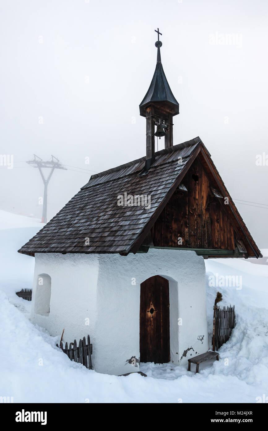 Kleine Kapelle und Schnee in den Bergen Stockbild