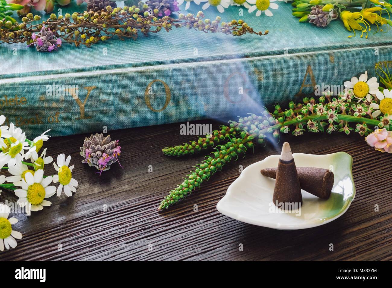 Abgenutzte Yoga Buch mit Blumen und Weihrauch auf dunklem Holz Tisch Stockbild