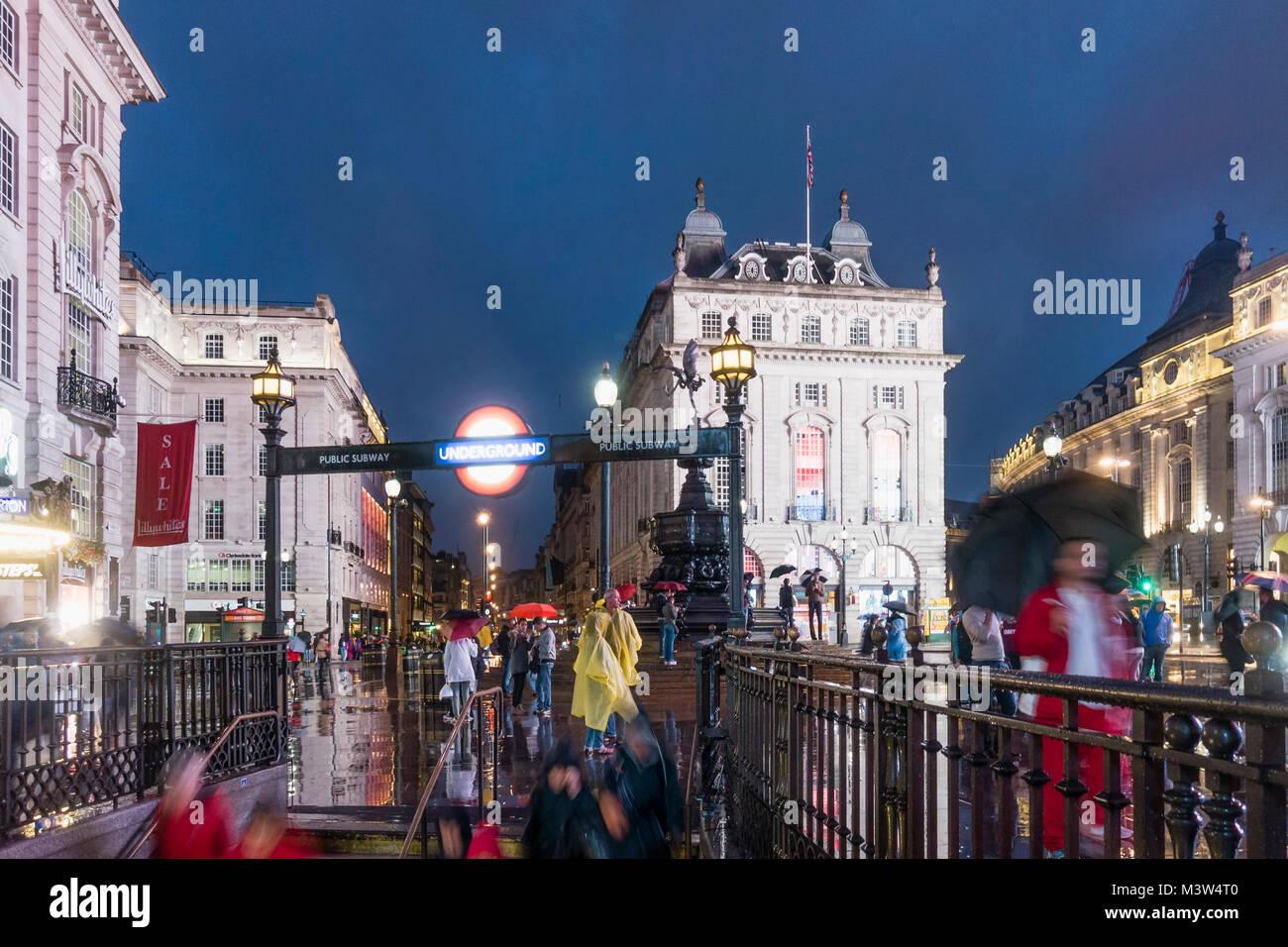 Menschen mit Sonnenschirmen, Piccadilly Circus, Regen, abends, in der U-Bahn Eingang, London, UK Stockbild