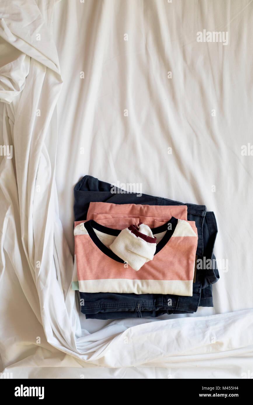 Hohe Betrachtungswinkel eines gefalteten T-Shirt, ein Paar Socken und eine Hose auf dem weißen Laken des ungemachten Stockbild
