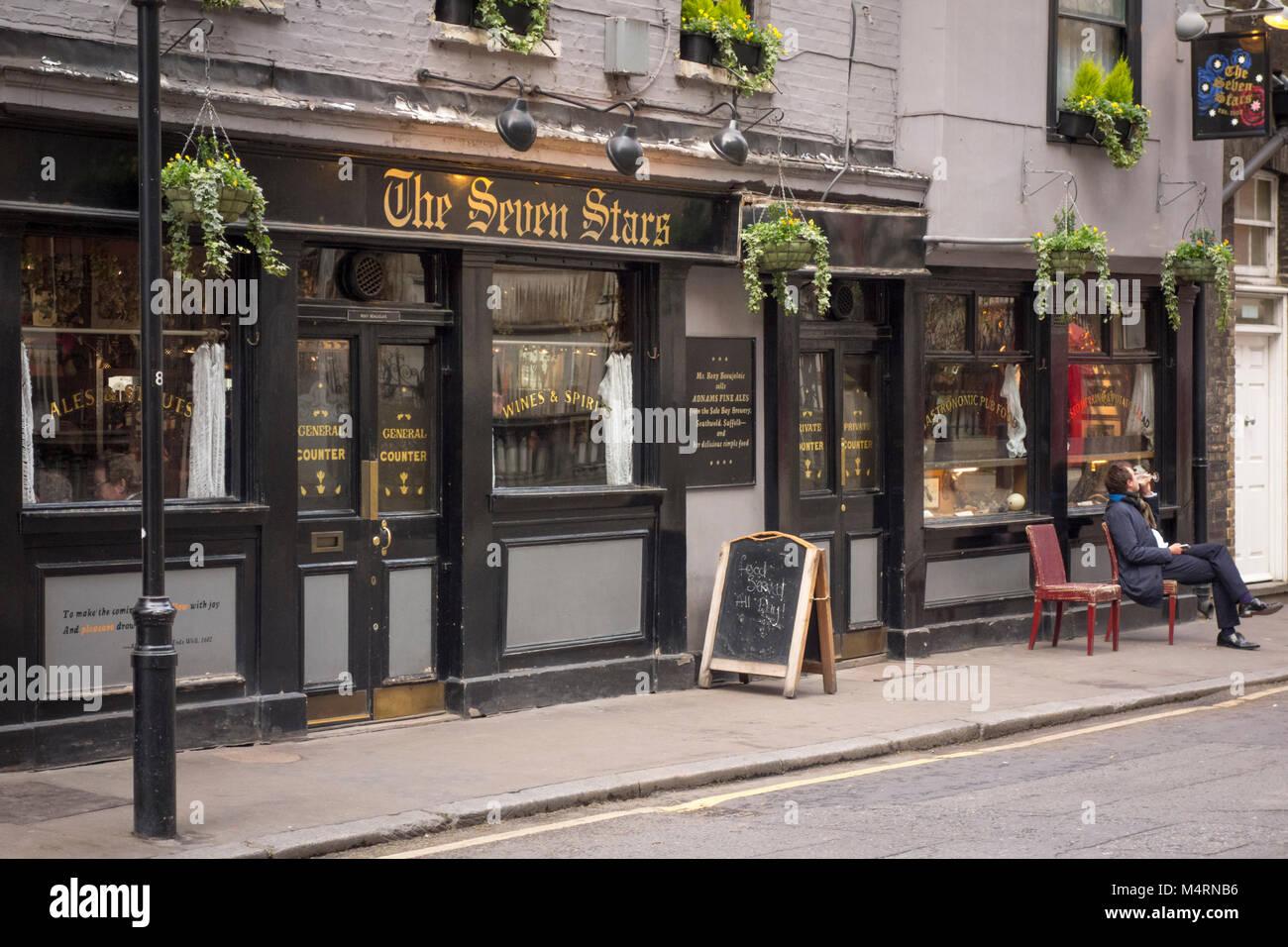 Mann trinken außerhalb der Sieben Sterne Pub, Carey Street, Holborn, London, UK Stockbild