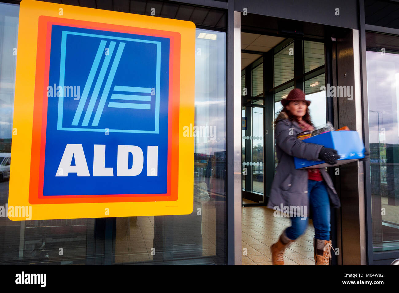 Frau mit Box shopping verlässt Aldi Stores in Letterkenny, County Donegal, Irland Stockfoto