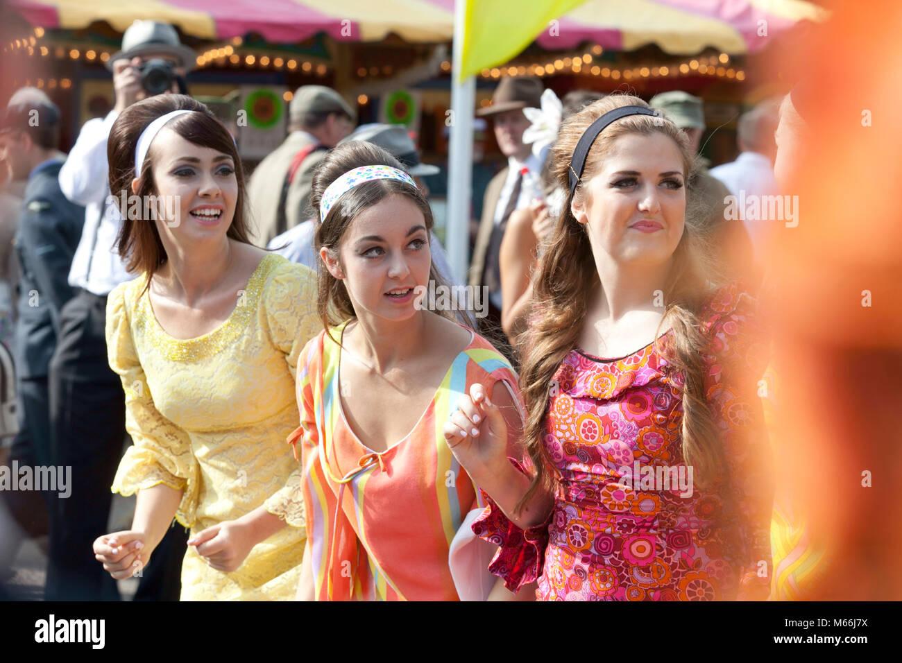 Drei junge Frauen in bunten 60er Style Kleider suchen gerne die Teilnahme an der Goodwood Revival Meeting Stockbild